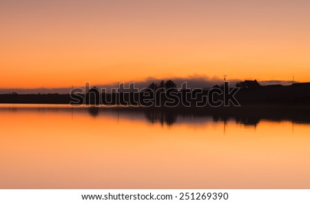 Skyline silhouette of a cottage at night over Dozmary Pool a natural lake on Bodmin Moor in Cornwall - stock photo