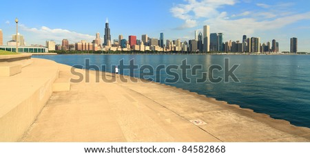 Skyline view of downtown Chicago from the Lake Michigan lakeshore trail with an early morning jogger running by. - stock photo