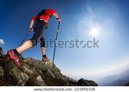 Skyrunning: rear view of a young male runner walking along a mountain trail. Sunny summer day. West Alps, Italy, Europe. - stock photo