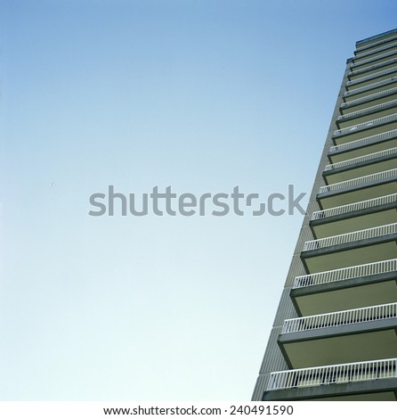 Skyscraper balconies against blue sky - stock photo