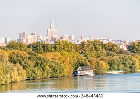 Skyscraper behind bridge and riverside with growth and pier before. Moscow, Russia.  - stock photo