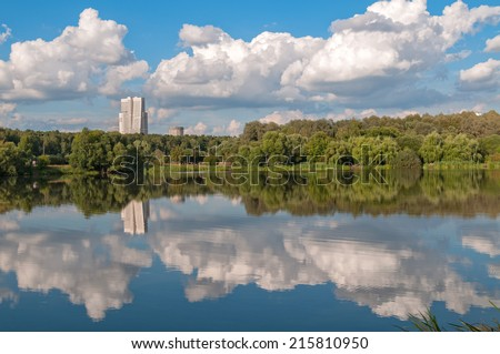 Skyscraper behind forest reflecting in lake before against blue sky background. Moscow, Russia.