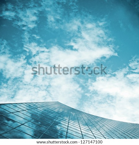 skyscraper glass reflecting cloudy sky  ; abstract business background - stock photo