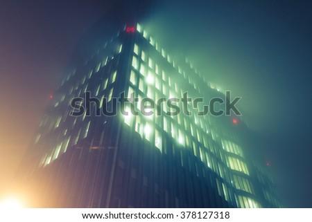 Skyscraper in fog with glowing windows at night - stock photo