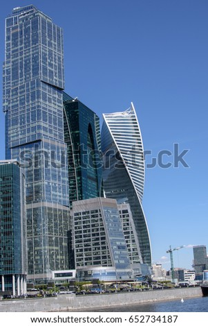 Skyscraper of metal and glass in a big city near the river.