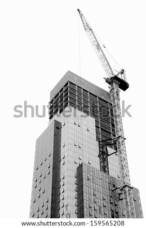 Skyscraper under construction with crane on white background. B&W