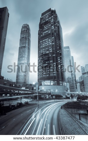 Skyscraper with traffic motion blurred lights in the night in Hong Kong, Asia. - stock photo
