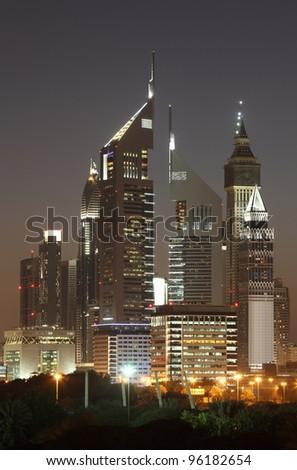 Skyscrapers in Dubai illuminated at night - stock photo