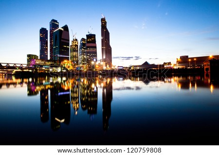 Skyscrapers Moscow business centre (Moscow City) at evening with water reflections. - stock photo