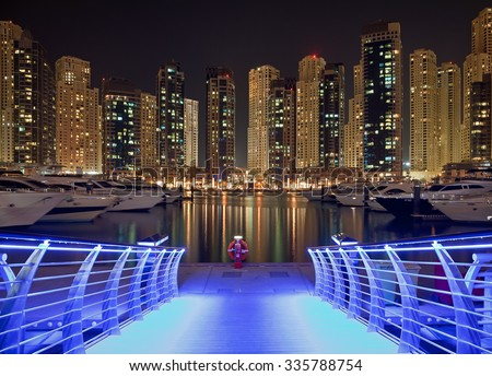 Skyscrapers of Dubai Marina against black sky, behind a pier bridge illuminated with blue light. Dubai Marina is an artificial canal city, carved along a two mile stretch of Persian Gulf shoreline. - stock photo
