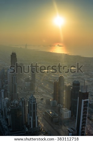 Skyscrapers of Dubai UAE during sunset. Aerial view of Dubai and Arabian gulf against the sun with lens flare - stock photo
