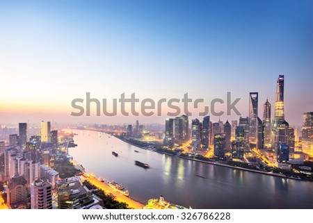 skyscrapers of the city in China surrounded by a river at dusk - stock photo