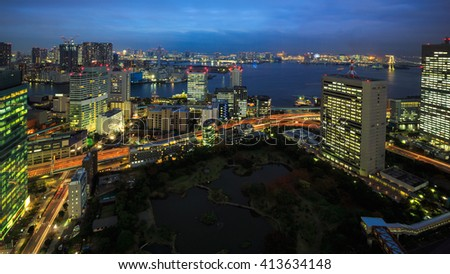 Skyscrapers starting to get light up at night in downtown Tokyo, Japan - stock photo
