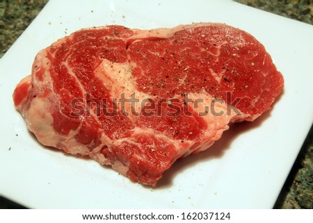 Slab of Raw Steak with Salt and Pepper