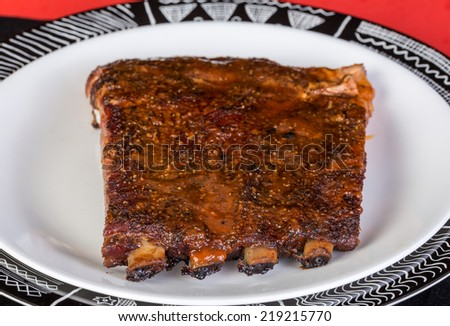 Slab of spicy beef ribs rubbed in various pepper and spices and grilled to perfection.  Black; white and red plate and background in Southwestern Graphics. - stock photo