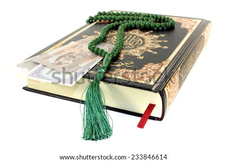 slammed Quran with Pakistani currency before light background - stock photo
