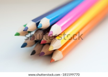 Slanting colorful wooden crayons on white background, macro with shallow dof. Selective focus. - stock photo