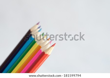 Slanting colorful wooden crayons on white background, tips of pencils macro with shallow dof. - stock photo