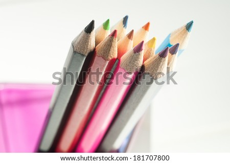 Slanting colorful wooden crayons on white background, tips of pencils, macro with shallow dof. Selective focus. - stock photo