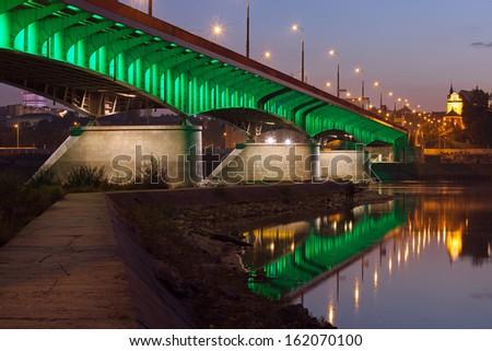 Slasko-Dabrowski bridge illuminated at dusk with reflections on water and pier on the Vistula river in Warsaw, Poland. - stock photo