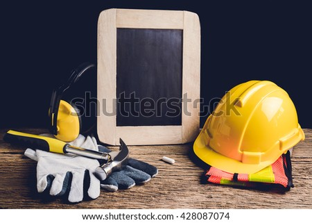 slate board, protective clothing and Hand Tool on wooden background