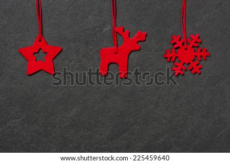 Slate board with three christmassy felt figures - stock photo