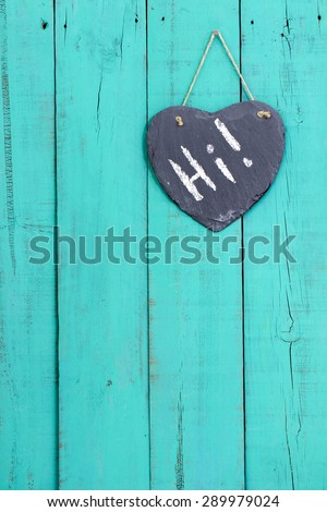 Slate heart with Hi hanging from rope on rustic antique teal blue wooden background - stock photo
