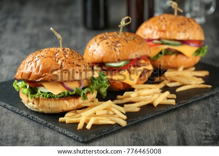 Slate plate with tasty burgers and french fries on table