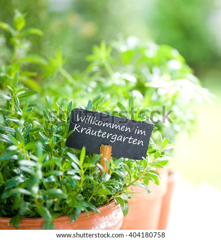 Slate with german text: Welcome to the herb garden