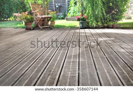 slats of a wooden terrace overlooking garden - stock photo