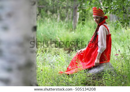 Slav in traditional dress is sitting in nature