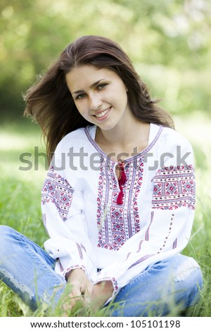 Slav teen girl at green meadow in national ukrainian clothing. - stock photo