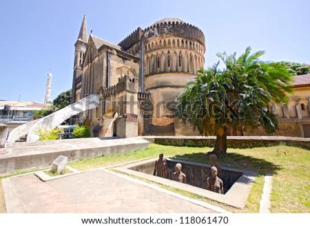 Slave Market Memorial with Church in the Background in Stone Town on Zanzibar Island - Tanzania - stock photo