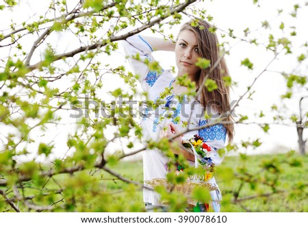 Slavic girl in Ukrainian shirt hiding behind a tree - stock photo