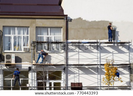 Slavyansk-na-Kubani, Russia - September 9, 2016: Plasterers Builders plastered wall in a commercial building. Work on scaffolding.