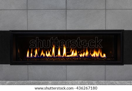 Sleek modern gas fireplace with gray tile surround and black glass media reflecting the flames - stock photo
