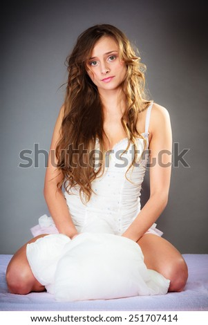 Sleep and wake up concept. Pretty young woman in curly long brown hair with pillow on gray background. - stock photo