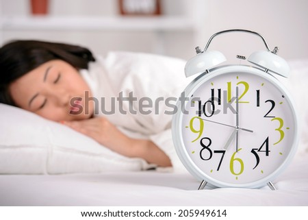 Sleep. Portrait of Asian woman sleeping on the bed at home. Great alarm clock in the foreground - stock photo