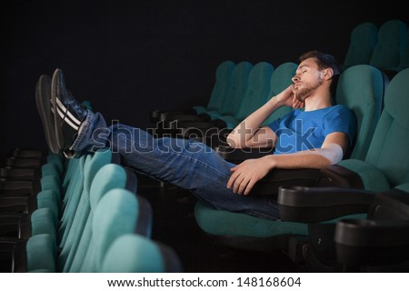 Sleeping at the cinema.  Side view of young men sleeping at the cinema and holding his hand on chin