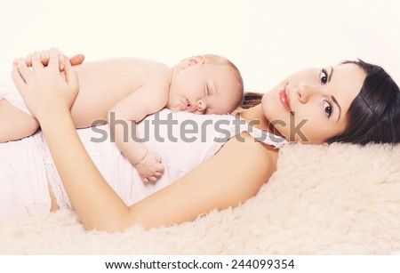 Sleeping baby and mother at home - stock photo