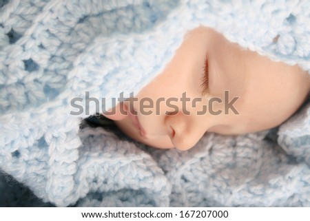 Sleeping baby boy wrapped in a wool blanket - stock photo