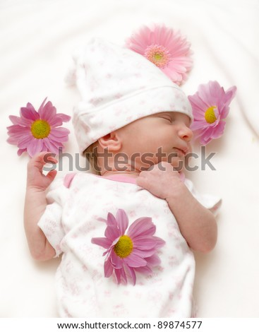 Sleeping baby girl infant with daisies on white blanket
