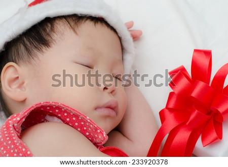 Sleeping baby girl Santa Claus - stock photo