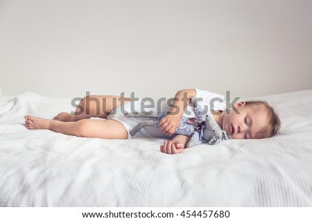 Sleeping baby in his crib, holding a teddy bear.