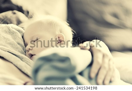 Sleeping baby in mother's arms. - stock photo