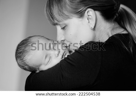 Sleeping baby on the mother's hands. Young mother shakes her baby in her arms and kisses him - stock photo