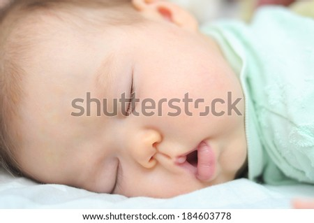 sleeping baby portrait close up at night with open mouth, cute and adorable newborn baby face, baby health care