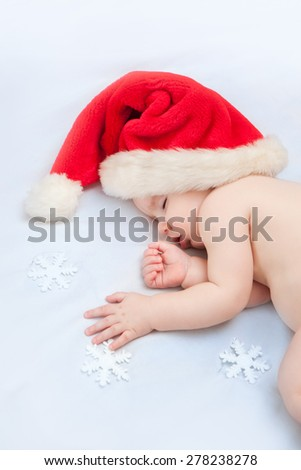 Sleeping baby Santa Claus red hat and holding Christmas tree decoration - stock photo