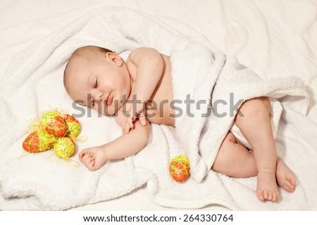 Sleeping baby with Easter eggs - stock photo