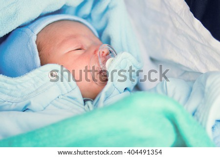 Sleeping baby with pacifier in a blue blanket - stock photo